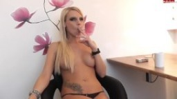 The busty blonde girl smokes a cigarette and touches her sexy big tits.